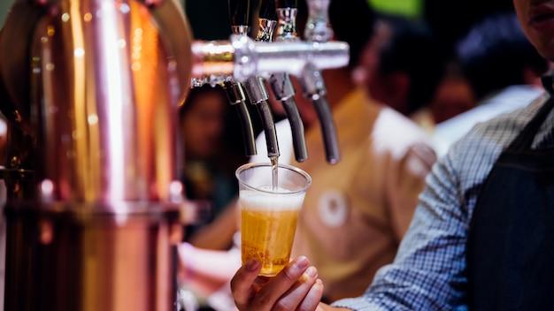 Barman ou barman versant une bière du robinet de bière Photo Premium