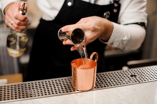 Barman en chemise blanche versant une portion de boisson alcoolisée dans une tasse Photo Premium