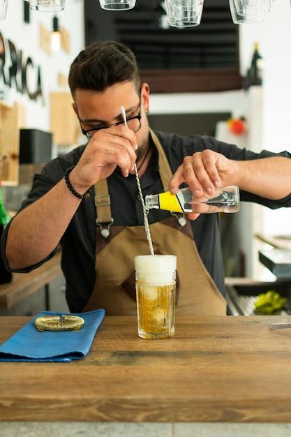 Barman dans un pub ou un restaurant préparant un cocktail au gin tonic. Photo Premium