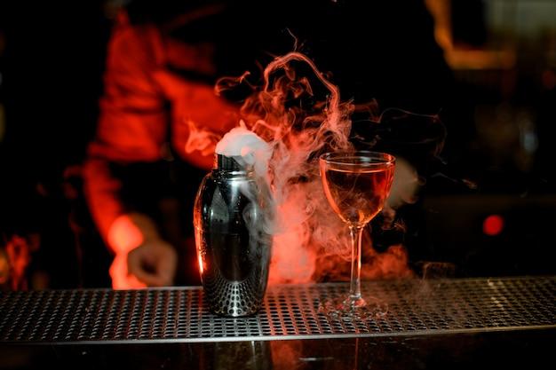 Barman debout au premier plan d'un cocktail dans le shaker en verre et acier fumé Photo Premium