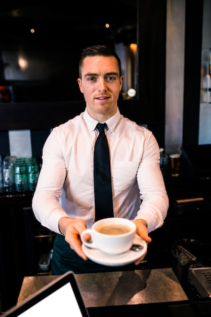 Barman donnant un café à un client dans un bar Photo Premium