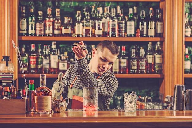 Barman Faisant Un Cocktail Alcoolisé Au Comptoir Du Bar Sur Le Bar Photo gratuit