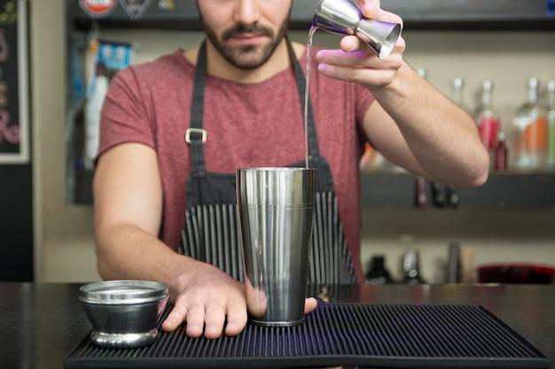 Barman faisant un cocktail au comptoir du bar Photo gratuit