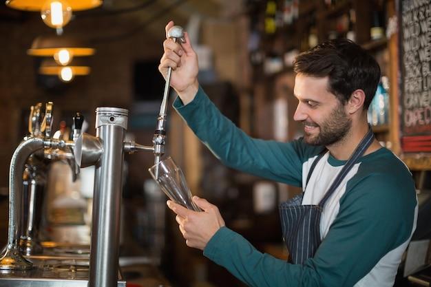 Barman Heureux, Verser La Bière Du Robinet Photo Premium