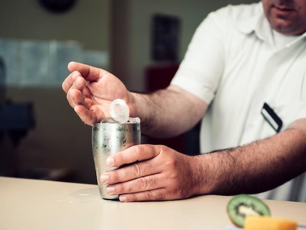 Barman mâle remplissant shaker avec des glaçons Photo gratuit