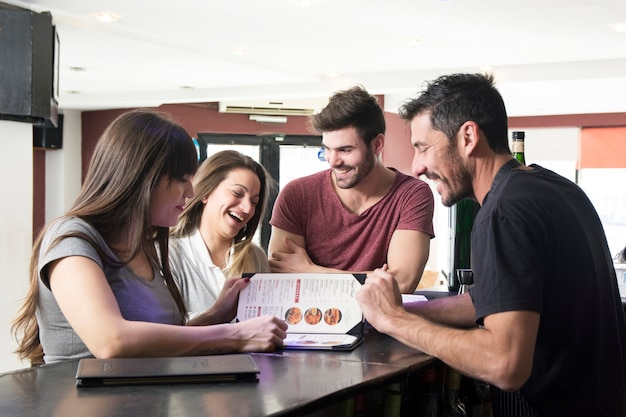 Barman montrant le menu aux clients au comptoir du bar Photo gratuit