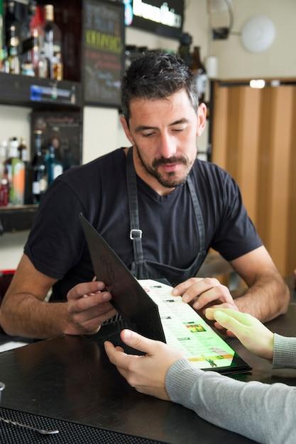 Barman montrant le menu à la clientèle féminine au comptoir Photo gratuit