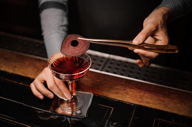 Barman préparant une boisson alcoolisée à décor rouge Photo Premium