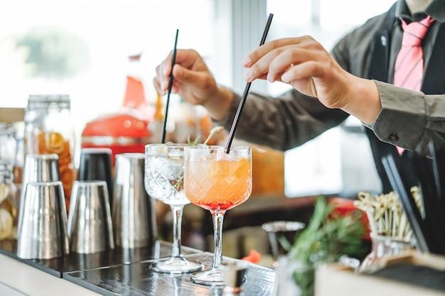 Barman préparant différents cocktails à mélanger avec des pailles à l'intérieur du bar Photo Premium
