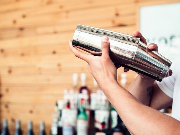 Barman prépare un cocktail dans un shaker Photo gratuit