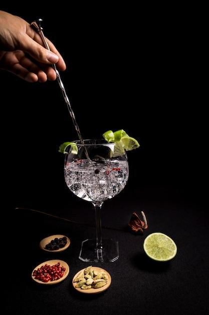 Barman prépare un cocktail de gin tonic sur fond noir Photo Premium