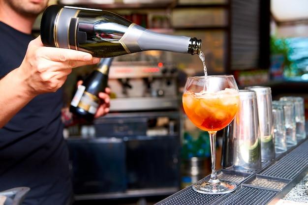 Le barman prépare des cocktails froids dans la discothèque. Photo Premium