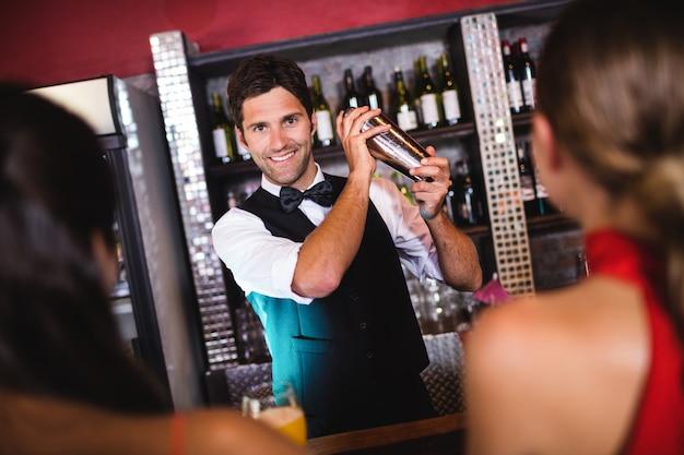 Barman secouant cocktail dans un shaker au comptoir Photo Premium