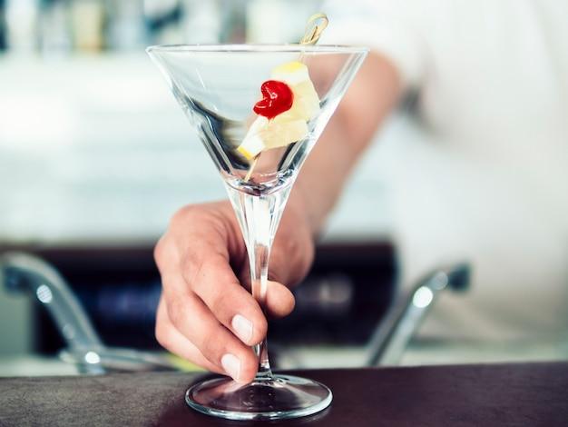 Barman servant un cocktail avec des fruits Photo gratuit