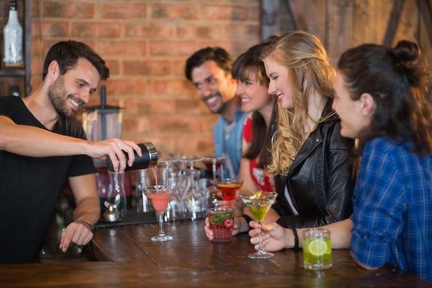 Barman Souriant Servant Des Boissons Pour Les Clients Photo Premium