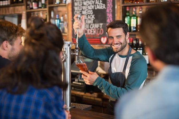 Barman Souriant, Verser De La Bière Dans Un Verre Pour Les Clients Photo Premium
