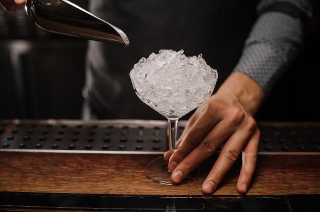 Barman tenant un verre à cocktail rempli de glace Photo Premium