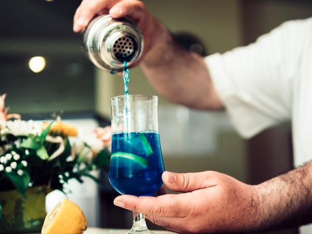 Barman versant une boisson alcoolisée en cocktail Photo gratuit
