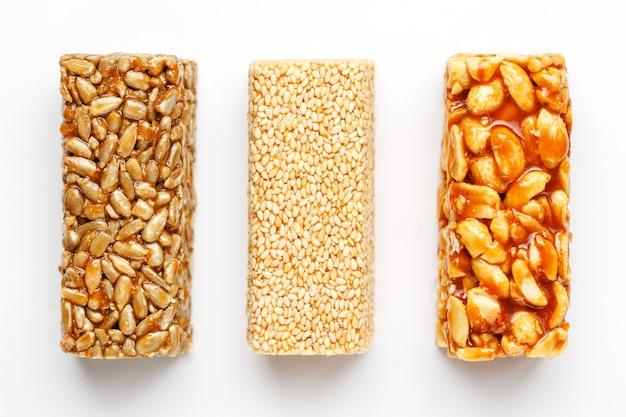 Barre de céréales avec des cacahuètes, du sésame et des graines. vue de dessus trois barres assorties, isoler Photo Premium