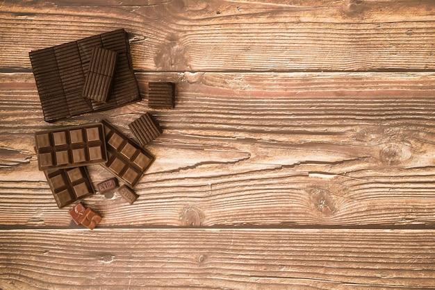 Barre de chocolat et des morceaux sur la table en bois Photo gratuit