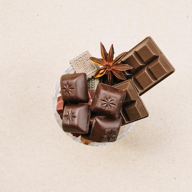 Barre de chocolat et morceaux de verre sur fond beige Photo gratuit