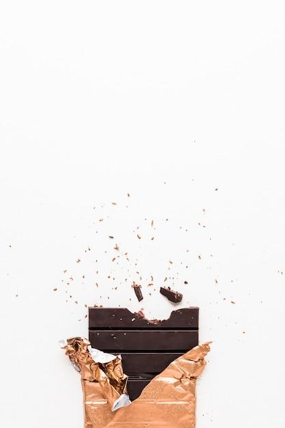 Barre de chocolat noir enveloppé dans du papier doré sur fond blanc Photo gratuit