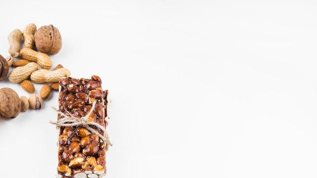 Barre de fruits secs saine énergie attachée avec une ficelle sur fond blanc Photo gratuit