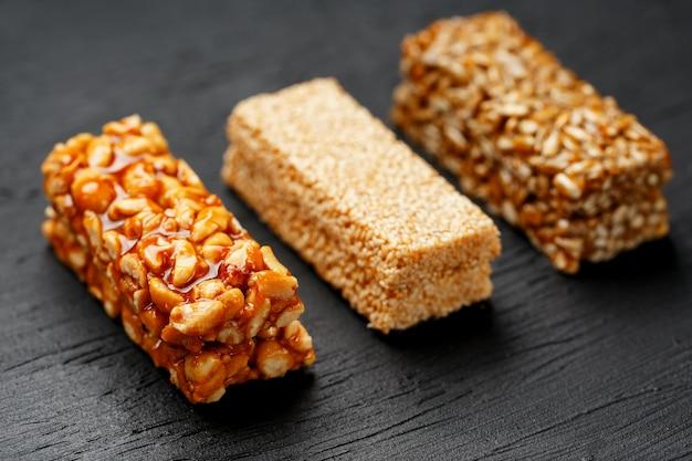 Barre granola de céréales avec des cacahuètes, des graines de sésame et de tournesol sur une planche à découper sur une table en pierre sombre. vue d'en-haut. trois barres assorties Photo Premium