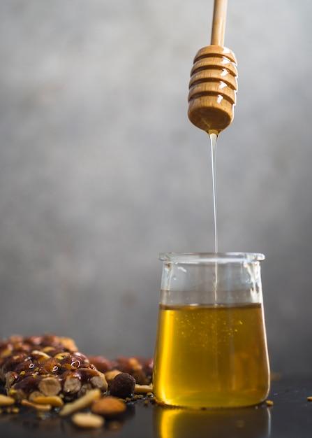Barre granola avec du miel dégoulinant d'une louche de miel en pot Photo gratuit