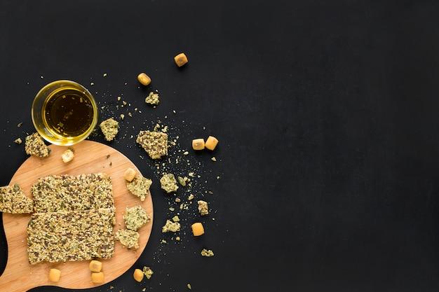 Barre granola avec de l'huile sur une planche à découper en bois Photo gratuit