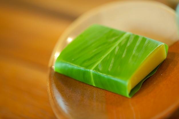 Barre jaune de savon enveloppé dans une feuille verte assis dans un porte-savon en bois Photo Premium