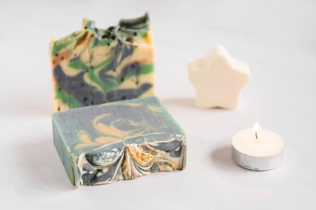 Barre de savon cassée avec une éponge étoile et une bougie illuminée sur fond blanc Photo gratuit