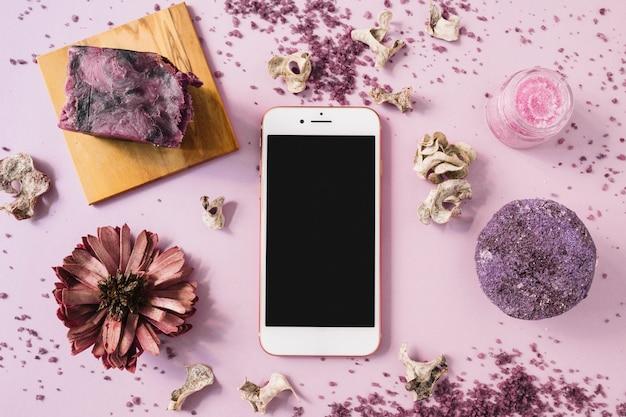 Barre de savon; gommage corporel aux herbes; fleur séchée et smartphone sur fond rose Photo gratuit