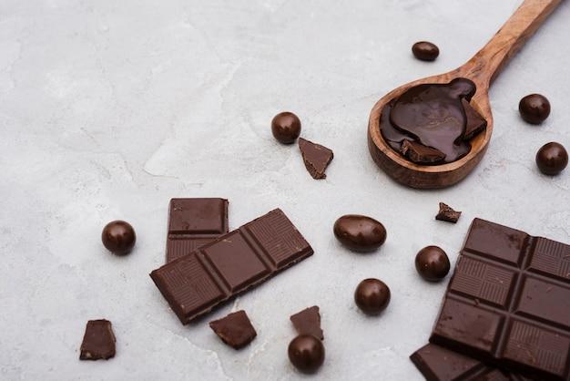 Barres de chocolat à angle élevé et cuillère en bois avec sirop de chocolat Photo gratuit
