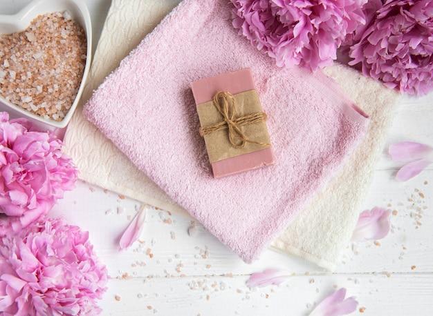 Barres de savon artisanal, serviettes douces et fleurs de pivoine Photo Premium