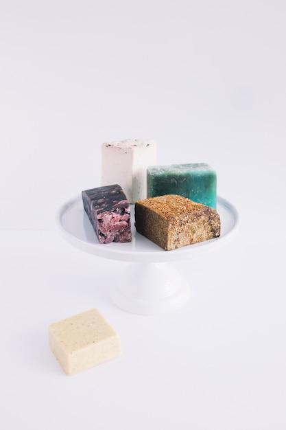 Des barres de savon colorées sur un gâteau se tiennent sur fond blanc Photo gratuit