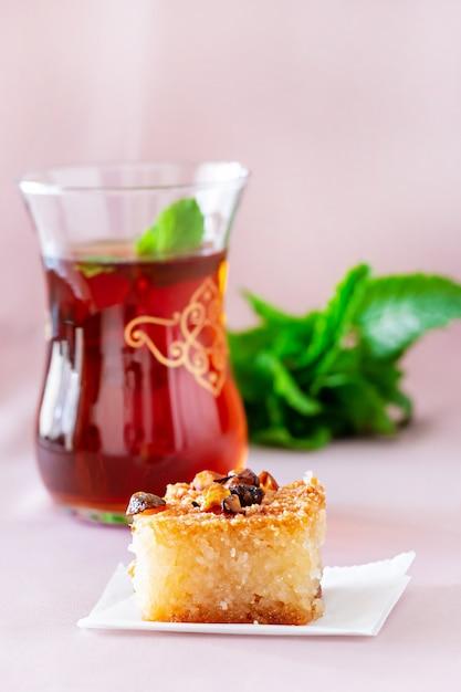 Basbousa ou namoora, dessert arabe traditionnel et thé à la menthe. délicieux gâteau de semoule maison. copier spase. mise au point sélective. Photo Premium