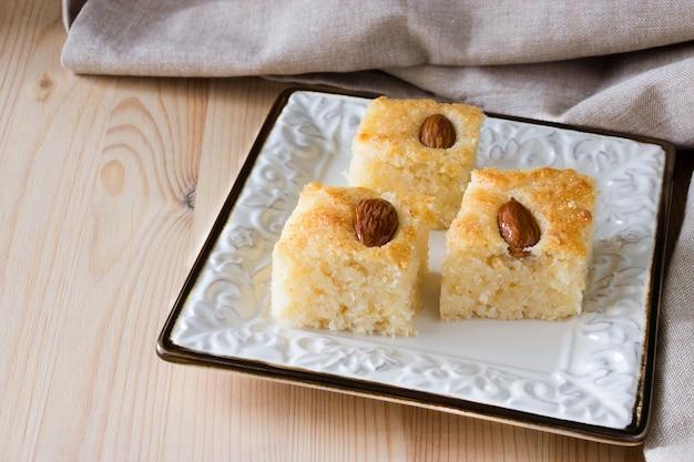 Basbousa (namoora) traditionnel gâteau de semoule arabe aux amandes et au sirop Photo Premium