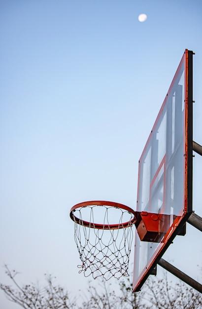 Basket-ball cerceau fond flou arbre et lune dans le ciel. Photo Premium