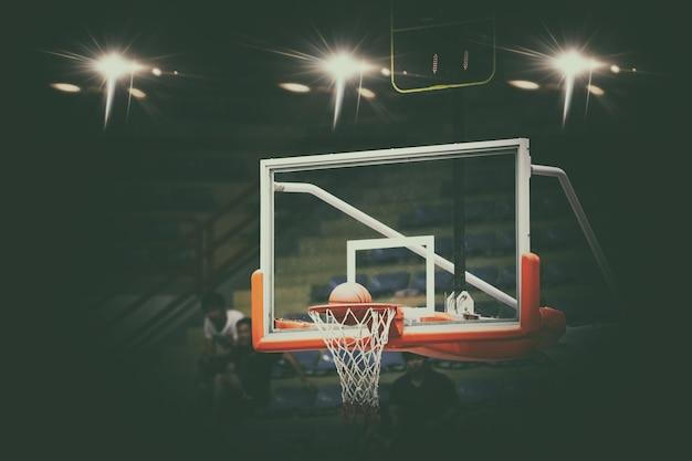 Basketball passant au filet et marquant pendant le match, flou et flou Photo Premium