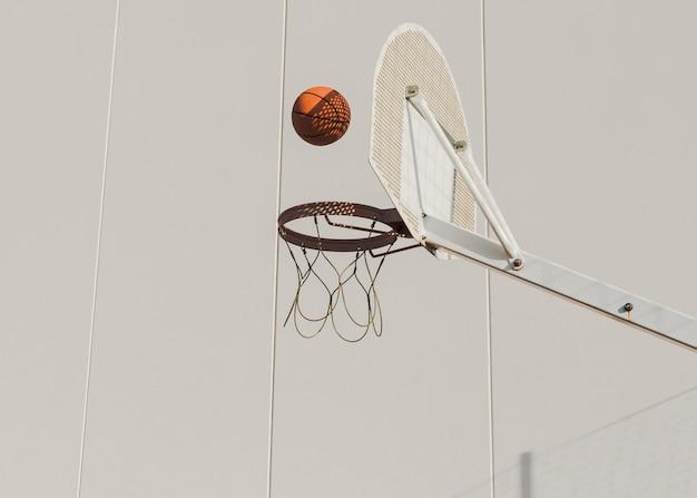 Basketball tombant dans le cerceau contre le mur Photo gratuit