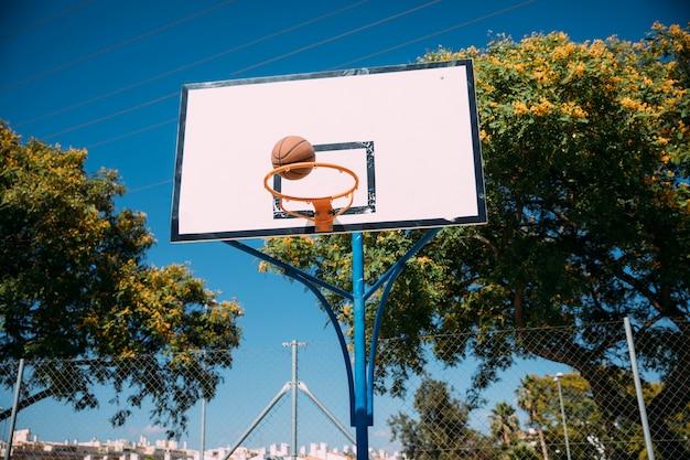 Basketball tomber dans le cerceau sur le ciel bleu Photo gratuit