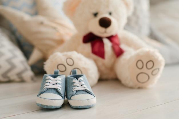 Baskets Bleus Pour Bébé Sur Le Fond D'ours En Peluche, Gros Plan Photo Premium