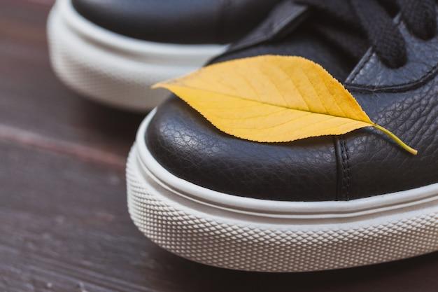 Baskets en cuir noir avec une feuille jaune sur fond en bois. concept d'automne Photo Premium