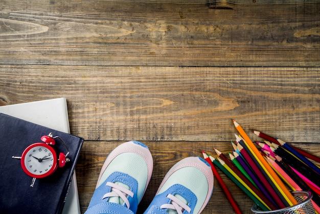 Baskets Pour Enfants, Livres, Crayons De Couleur Et Réveil Sur Fond De Bureau En Bois Photo Premium