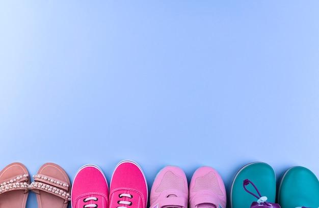 Baskets roses, bottes en caoutchouc et sandales pour fille sur fond bleu. chaussures différentes. Photo Premium