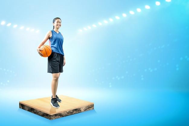 Basketteur femme asiatique tenant le ballon sur sa main Photo Premium