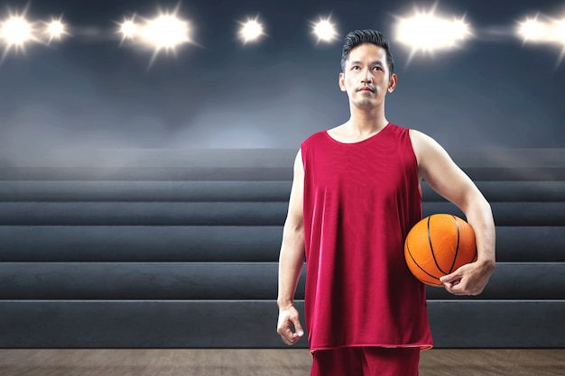 Basketteur homme asiatique tenant le ballon sur sa main Photo Premium