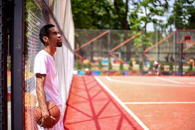 Basketteur noir posant dans le champ en plein air Photo Premium