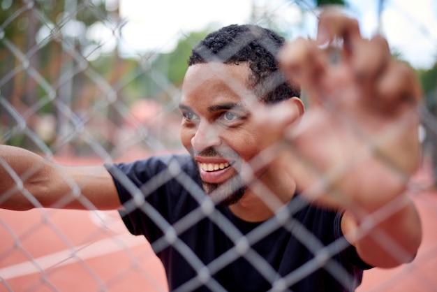 Basketteur noir tenant la palissade avec les mains Photo Premium
